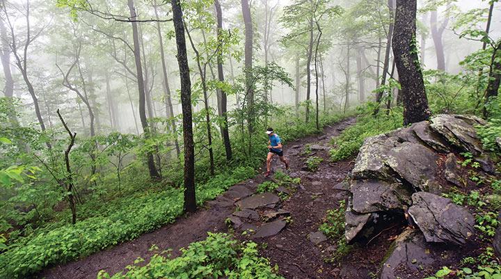 Scott Jurek running on a muddy section of the Appalachian Trail