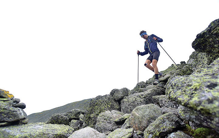 Scott Jurek running among lichen-covered rocks on the Appalachian Trail