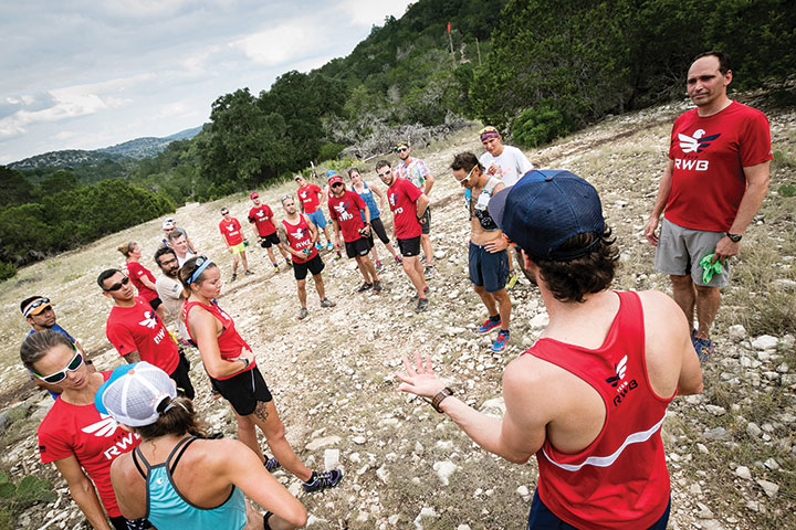 Just three months after the Team RWB trail-running camp, Chad Prichard smiles at an aid station midway through the Bandera 100K, his first ultra-distance trail race.